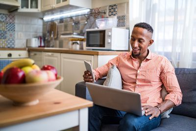 A man sitting in his kitchen with a laptop on his lap while holding a smartphone and smiling