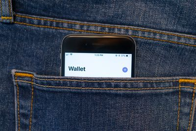 The Apple Wallet app on an iPhone sticking out of the pocket of some jeans