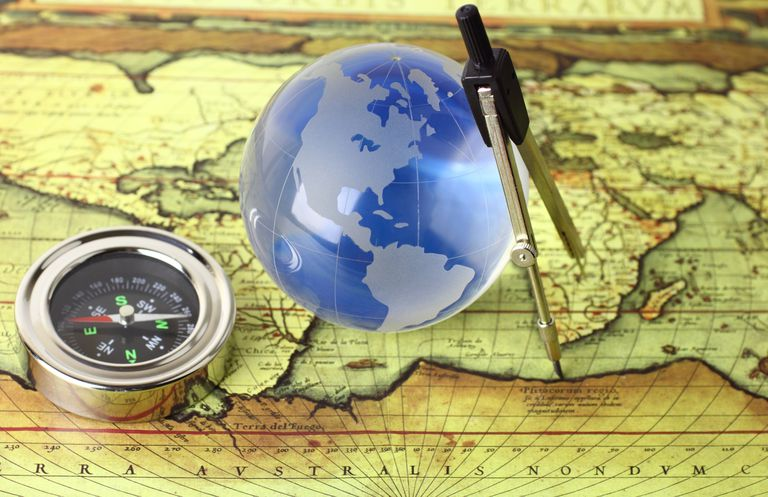 A compass, small globe and map are sitting on a table.