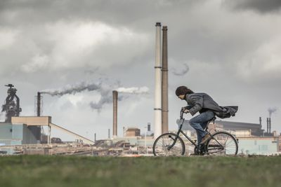 A cyclist biking past factories spewing out smoke from chimneys.