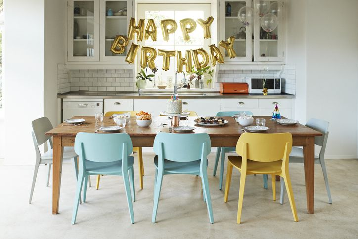 Chairs arranged around dining table in kitchen during birthday party at home