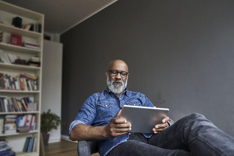 A man in an attic using an iPad.