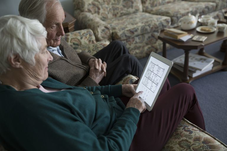 Elderly couple on couch playing Sudoku on an iPad