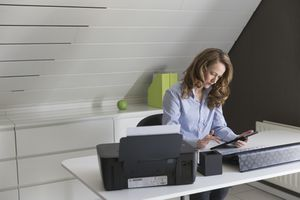 Woman at desk using tablet next to printer