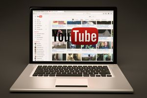Laptop with YouTube page on main screen, overlaid with YouTube logo