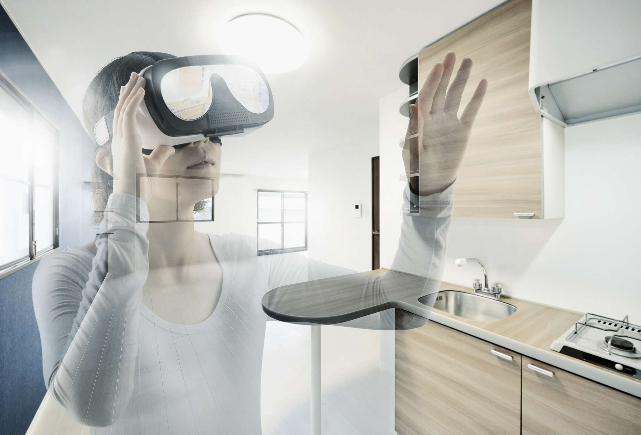 Someone wearing a virtual reality headset with and empty apartment overlayed on the image.