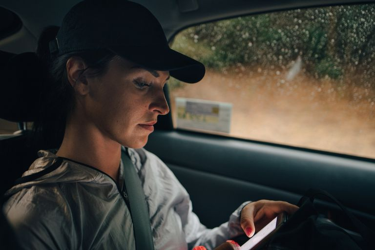 Woman sitting in car during a storm looking at weather alert on phone