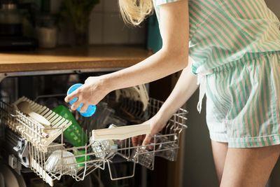 Woman loading a dishwasher