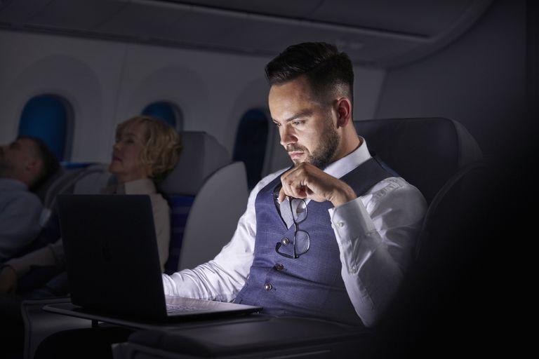 Businessman looking at email on plane