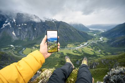 Man sitting at the top of a huge valley taking a photo with iPhone
