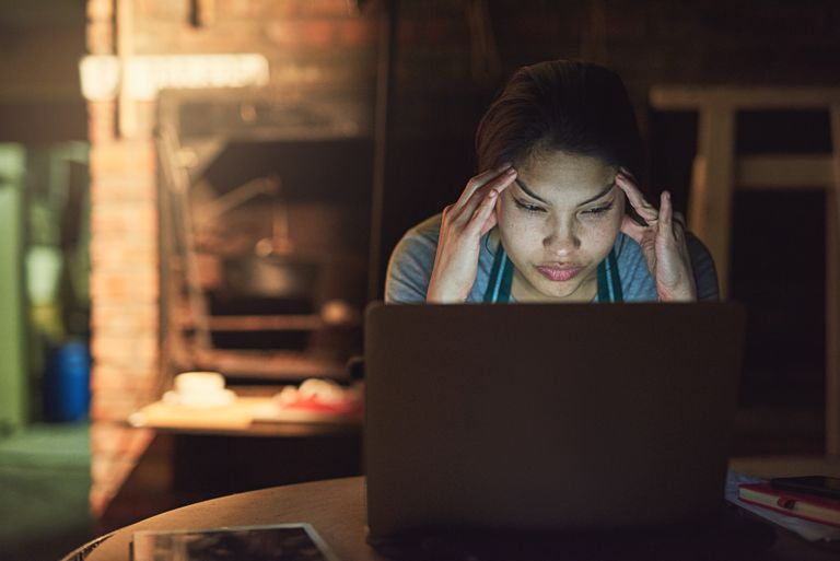 A woman with a frustrated facial expression is using a laptop computer