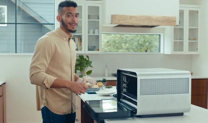 Man putting food into JuneOven