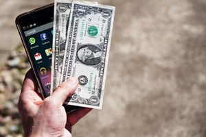 Person holding a smartphone and two dollar bills in one hand.