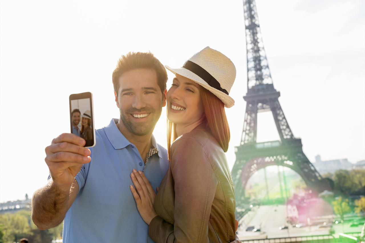 Two people taking a selfie with the Eiffel Tower in the background.