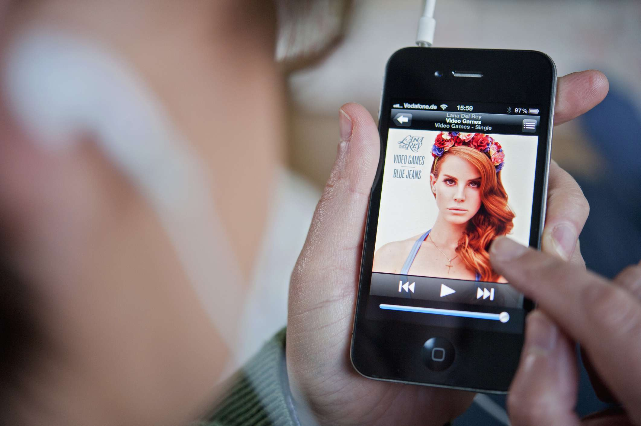 A closeup of an iPhone playing music.