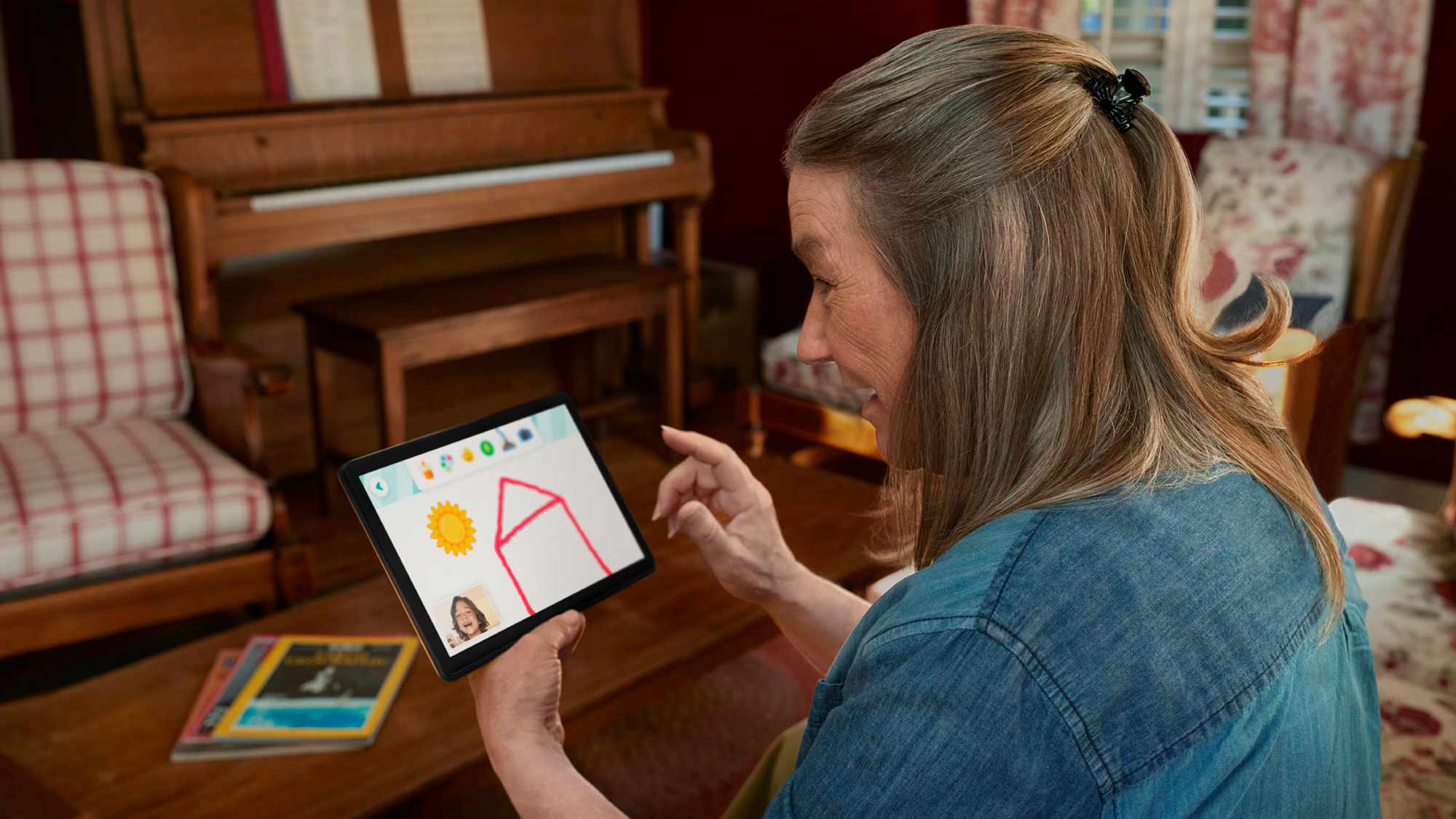 An adult interacting a child using the Amazon Glow app on a small tablet.