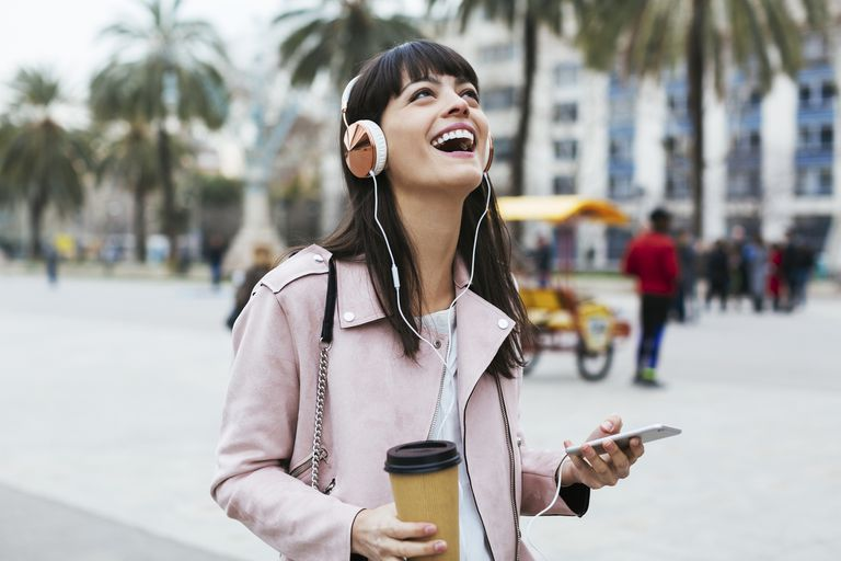 woman laughing and listening to music on her smartphone
