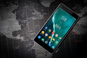 Android phone on a black and white map of the world