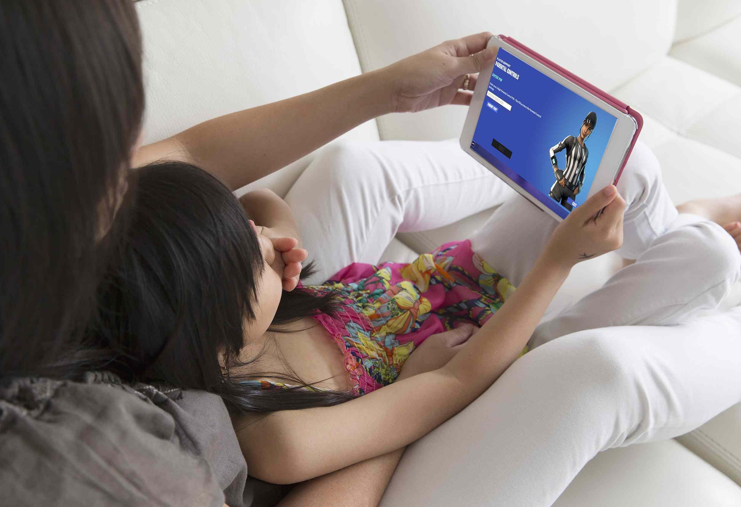 A mom sets up Fortnite parental controls on her child's tablet.