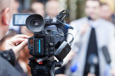 Photograph of man operating a professional video camera outdoors