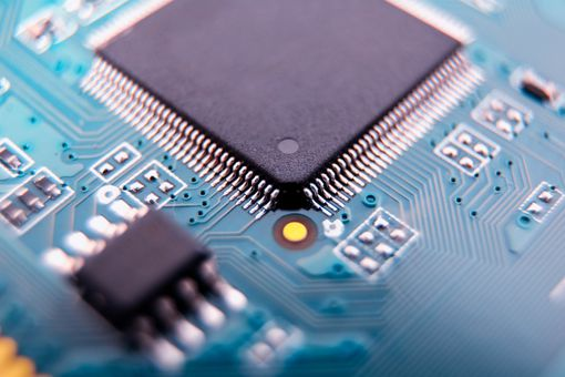 A green computer hardware printed circuit board (PCB) with a closeup of a processor