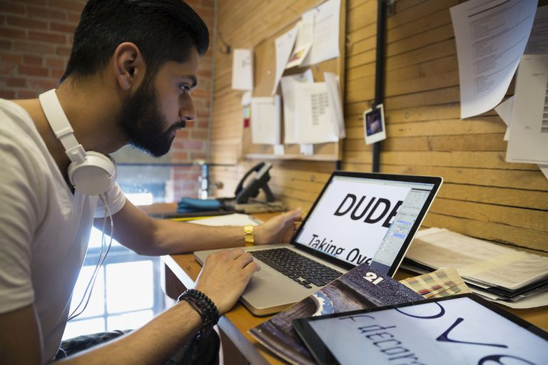 Designer examining fonts on laptop in office