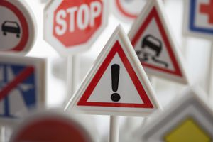 A toy hazard sign surrounded by other various road warning signs