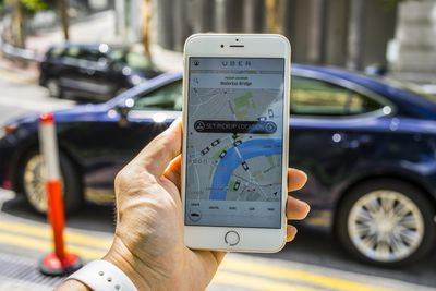 A photo of a person's hand holding a smartphone with the Uber app opened and displayed on the screen. The featured Uber app screen is asking the user to set a pickup location. The person is standing on a sidewalk in front of a parked car.