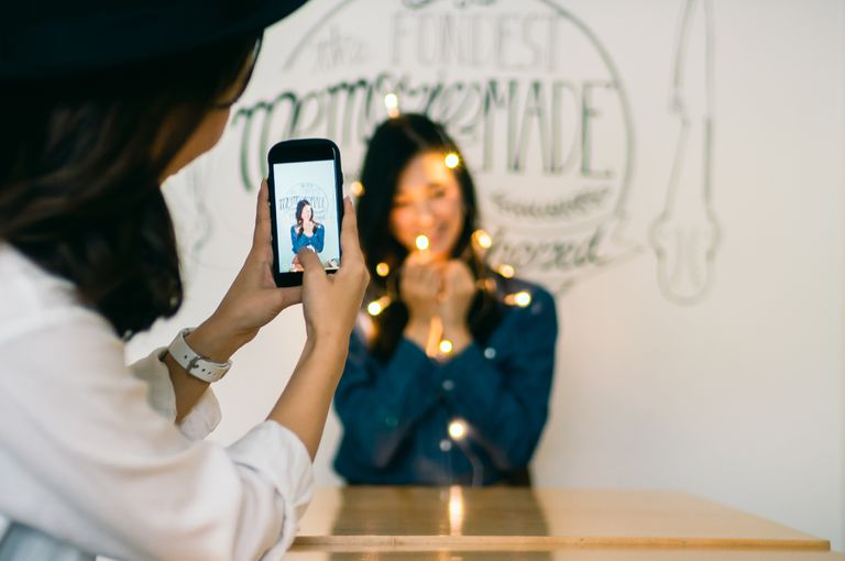 Young woman photographing a young woman Holding Illuminated Led Lights In bright room