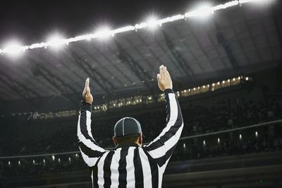 Football referee signaling touchdown in stadium