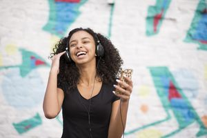 Person listening to a mobile phone with wired headphones and smiling