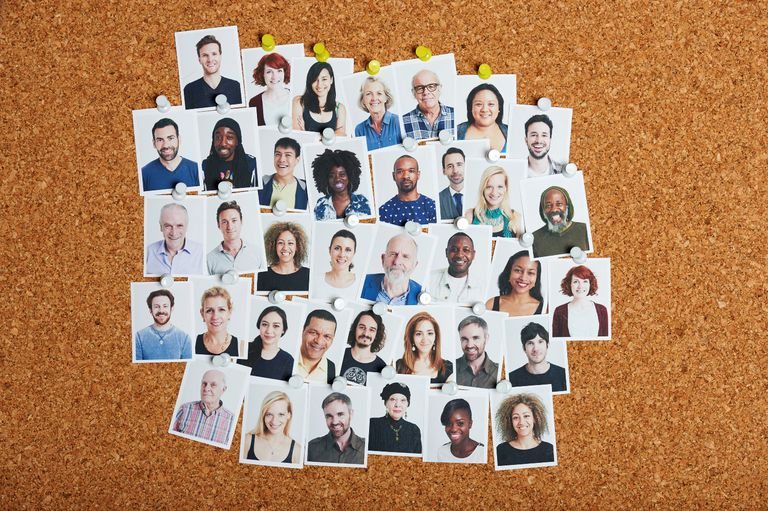 Many small photographic headshots of people thumbtacked to a corkboard