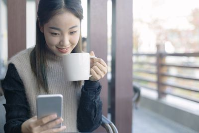 Woman drinking coffee and using smartphone