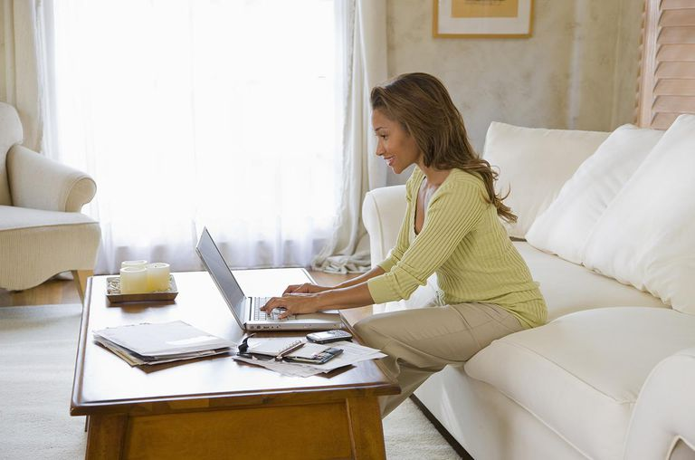 Woman sitting on sofa using laptop