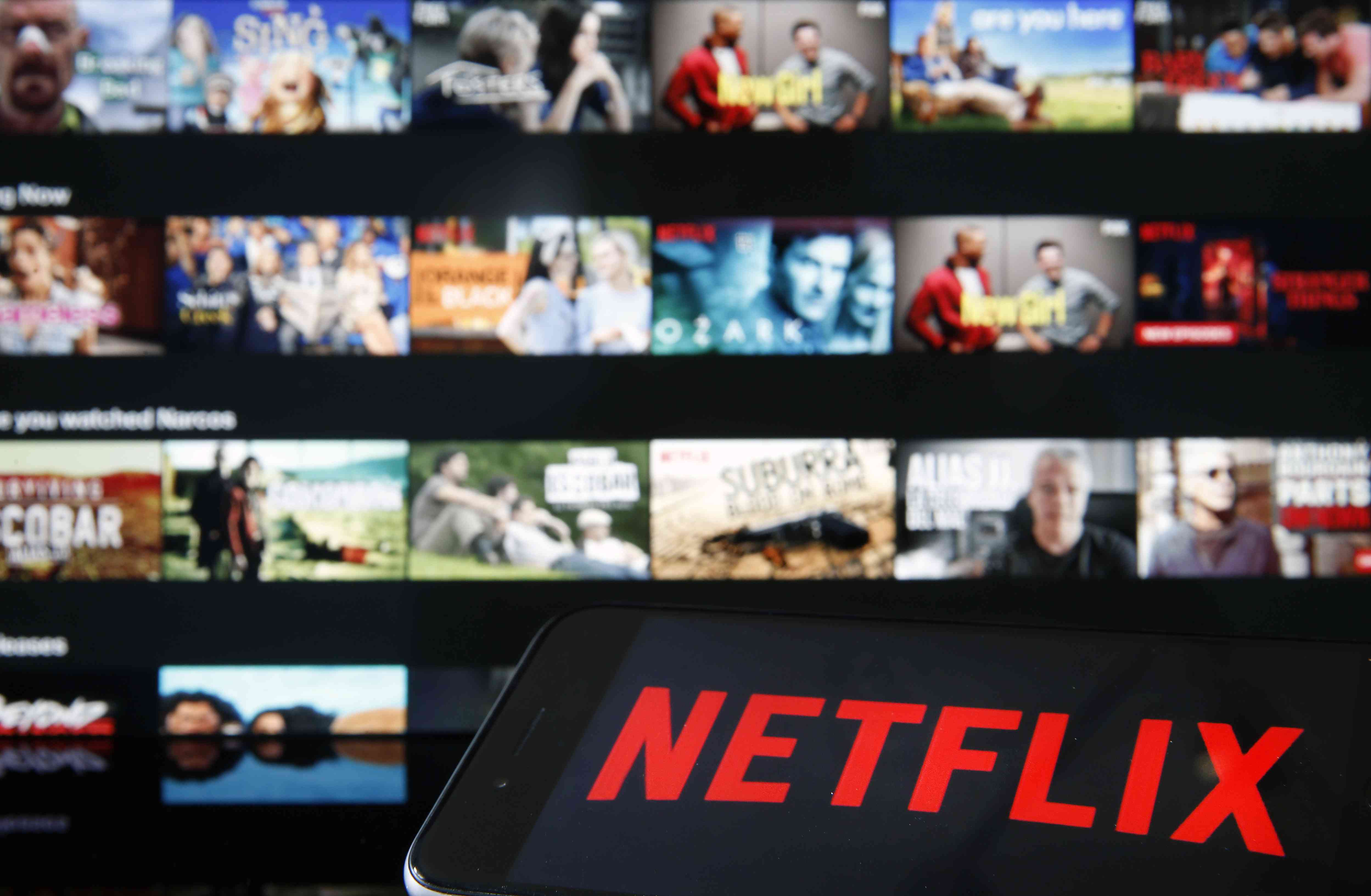 Netflix logo displayed on an iPhone in front of a television showing Netflix