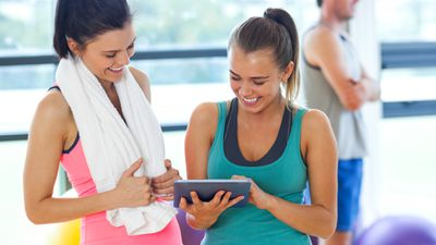 Two women in a gym using an iPad and a workout app