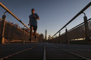 A jogger runs in the Hudson River Park at sunset in New York City