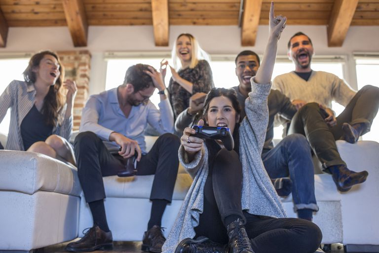 A group of people sitting on a couch react to their friends playing a video game.