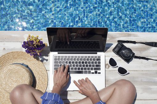 A woman sitting next to a swimming pool and using her MacBook Air.