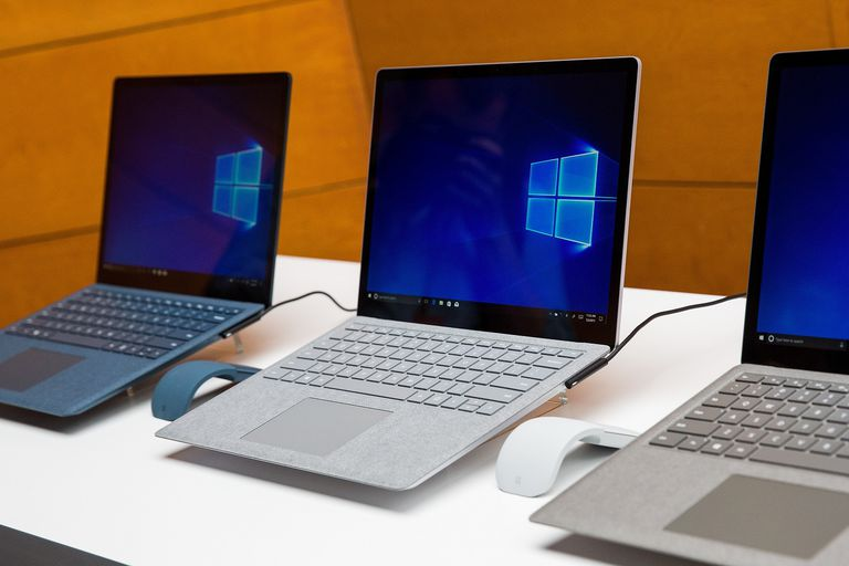 A photo of three Microsoft Surface laptops siting side by side. Each laptop appears to be running Windows 10.