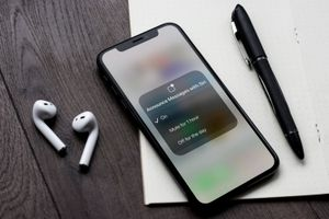 An iPhone with AirPods laying nearby with the screen to disable Announce Messages with Siri showing.