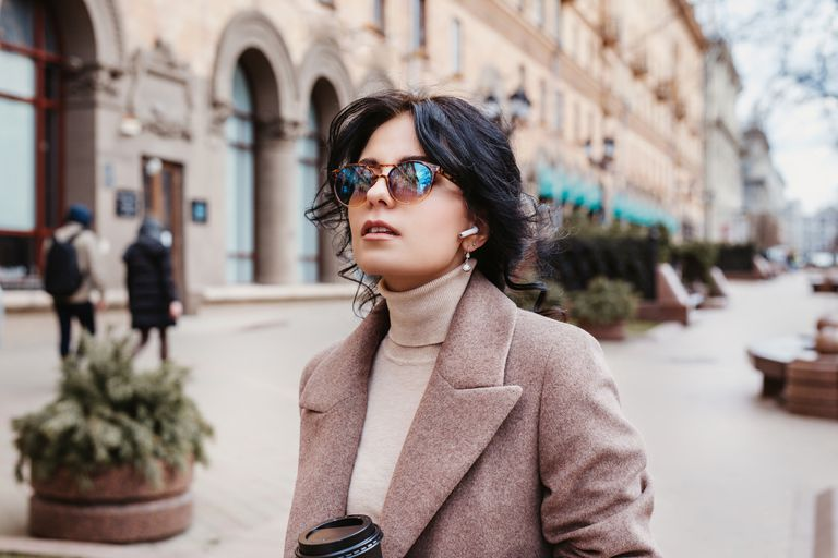 Stylish woman listing music on her airpods in city