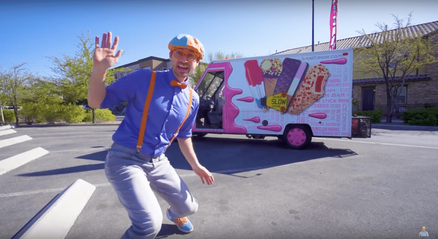 Blippi stands in front of an ice cream truck waving.