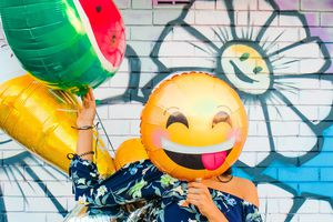 Woman covering face with smiling emoji balloon.