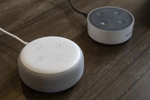 Two Alexa devices on a wooden table
