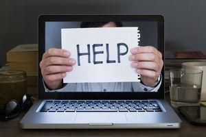 Photo of a man holding a HELP sign through a laptop screen
