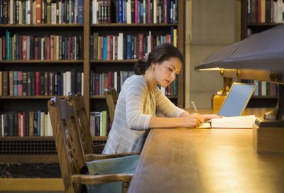 Woman using a Laptop in a Library working on a Research Paper on long wooden table