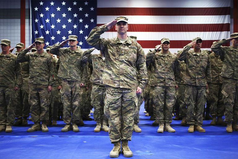 Soldiers from the U.S. Army's 3rd Brigade Combat Team, 1st Infantry Division, salute during the playing of the Star Spangled Banner during a homecoming ceremony in the Natcher Physical Fitness Center on Fort Knox on February 27, 2014 in Fort Knox, Kentucky. About 100 soldiers returned to Fort Knox after a nine-month combat deployment conducting village stability operations and working alongside Afghan military and police forces.
