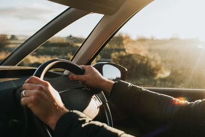 Hands holding a steering wheel in a car