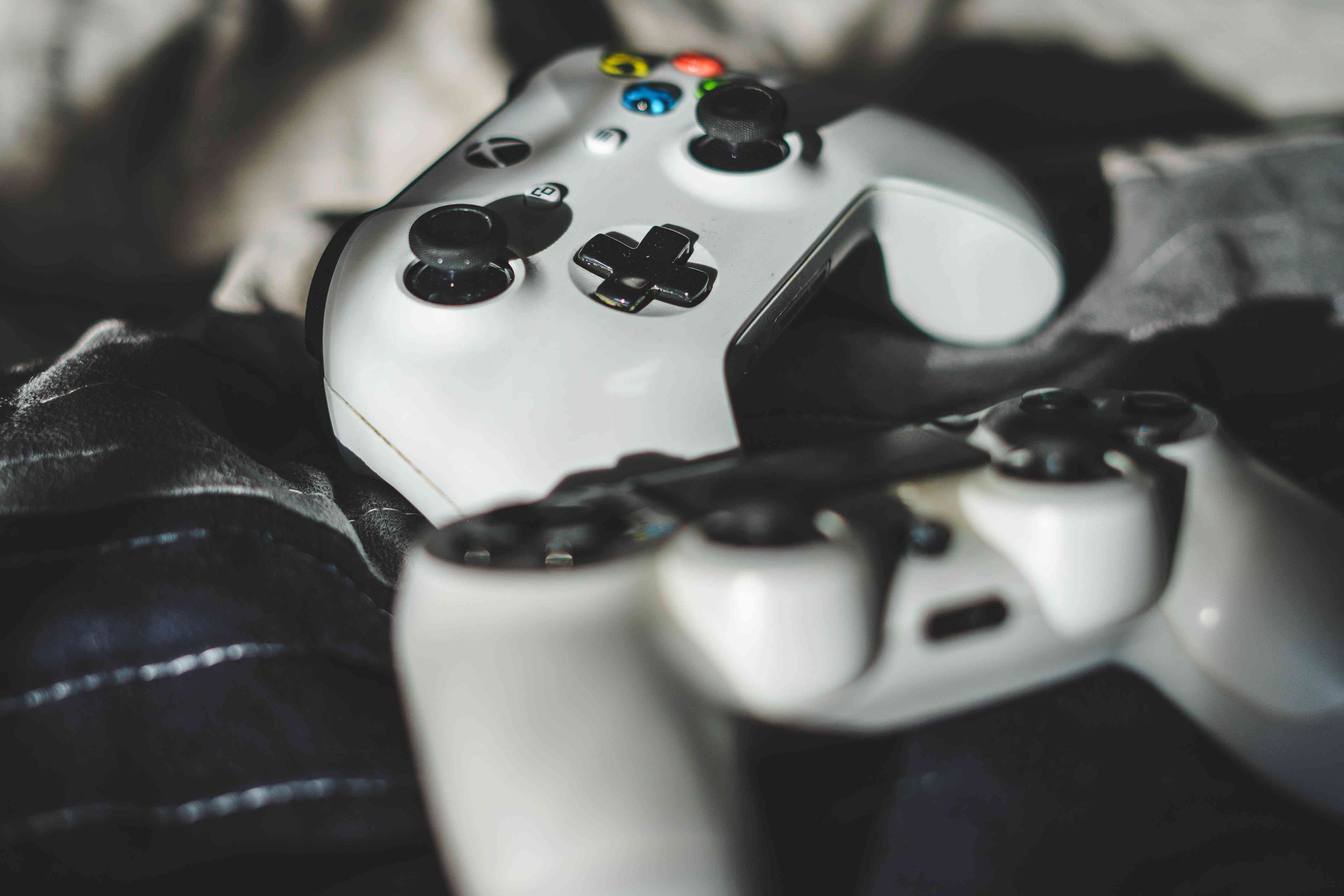 Xbox controllers laying on fabric.